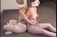 Két fiatal szőke lányt kötöznek össze félmeztelenül
